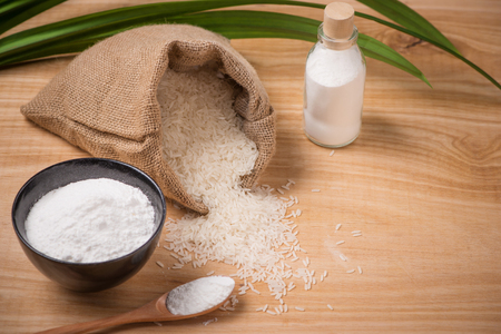 Jasmine white rice in sack and rice flour on wooden table. Stock Photo