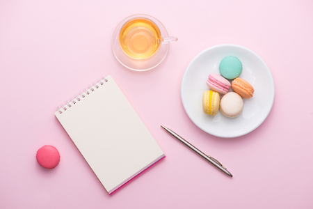 Flatlay of notebook, cake macaron, cup of tea and flower on pink table. Beautiful breakfast with macaroon.