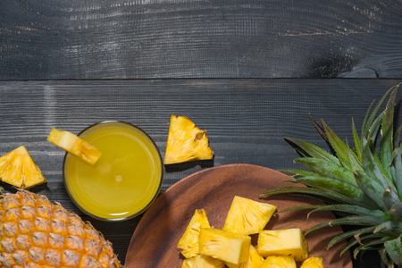 Top view of glasses of pineapple juice and pineapple fruit on a black wooden table Imagens