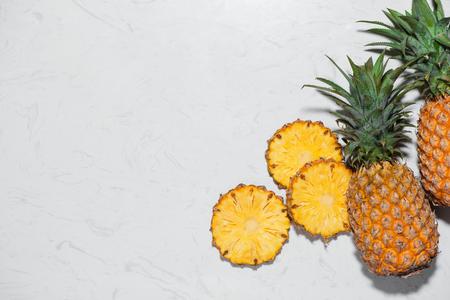 Bovenaanzicht van vers gesneden ananas op een marmeren achtergrond.