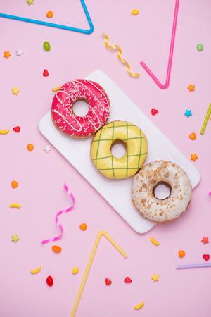 Feest. Verschillende kleurrijke suikerachtige ronde verglaasd donuts en flessen dranken op roze achtergrond. Stockfoto
