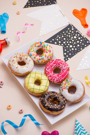 Party. Different colourful sugary round glazed donuts and bottles of drinks on light color background.