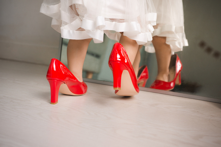 Cute funny little baby girl walks at home trying moms red high heel shoes Stock Photo