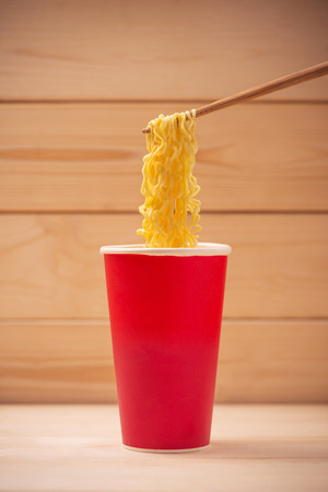 Eating Instant noodles in cup with a wooden chopstick.