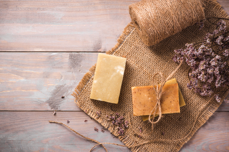 Natural soap with dried flowers on wooden background. Stock Photo
