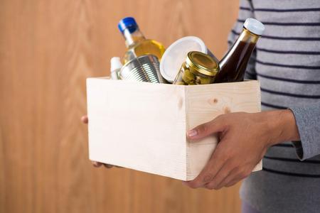 Volontario con scatola di donazione con ingredienti alimentari su fondo in legno Archivio Fotografico - 80529238