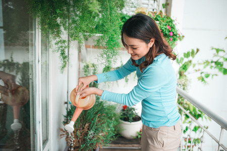 Kobieta wtering roślin w pojemniku na balkon ogród Zdjęcie Seryjne