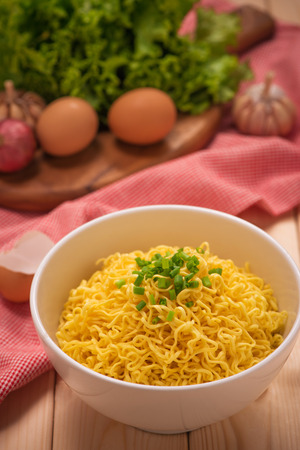 cooked instant noodle: Instant noodles in bowl with vegetables on wood background Stock Photo