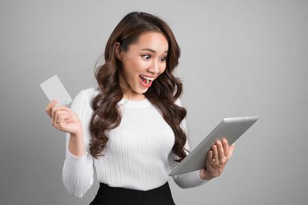 オンライン ショッピング、技術、電子マネーの概念。タブレット コンピューターおよびクレジット カードの幸せな若いアジア女性 写真素材
