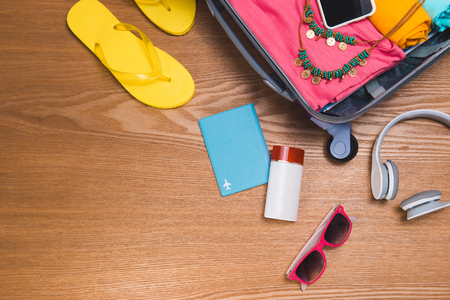 Travel and vacations concept. Open travelers bag with clothing, accessories, credit card, tickets and passport. Stock Photo