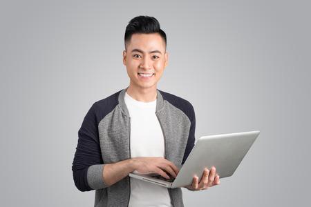 ノート パソコンを持って自信を持って若いアジア系のビジネスマン
