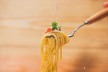 Close-up of asta spaghetti with tomato sauce, olives and garnish. Italian food.