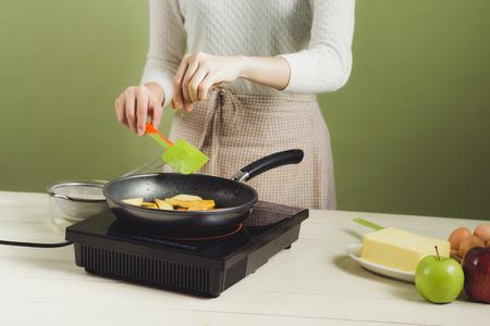 Huisvrouw die schort maakt. Stappen voor het koken van appeltaart. Scherpe groene appel.