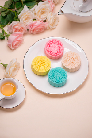 Sweet color of snow skin mooncake. Traditional mid autumn festival foods with tea on table setting. 免版税图像
