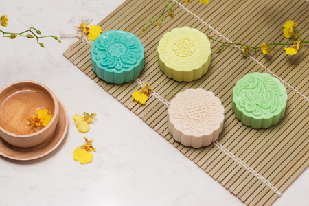 Sweet color of snow skin mooncake. Traditional mid autumn festival foods with tea on table setting. Stock Photo