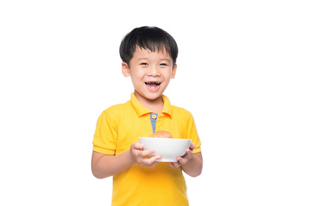 Happy Asian boy holding red apple in bowl.