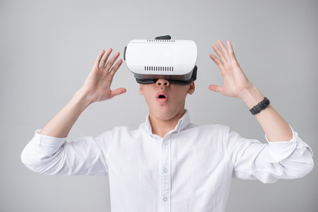 Excited asian man in a VR goggles and gesturing with his hands