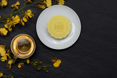 눈이 피부의 달콤한 색상 어두운 배경에 꽃 mooncake와 차 컵.