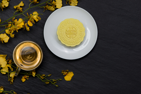 Sweet color of snow skin mooncake and tea cup with flowers on dark background. Stockfoto