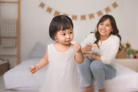 家でクッキーを食べるかわいい女の子