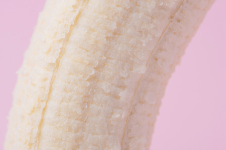 Detail of peeled banana on pink background Stock Photo