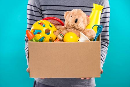 男性ボランティアでは、古いおもちゃで募金箱を保持しています。