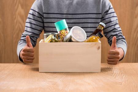 Volontario con casella di donazione con prodotti alimentari su sfondo di legno Archivio Fotografico - 81072512