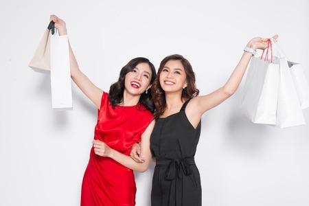 白い背景の上に買い物袋を 2 つ幸せの魅力的な若い女性