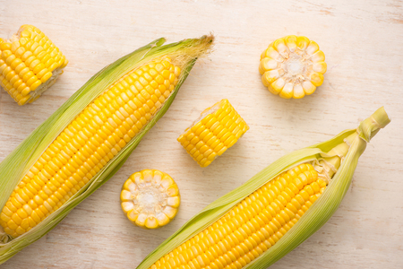 Sweet corns. Fresh corn on cobs on wooden table.