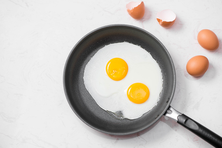 Top view of traditional healthy easy quick breakfast meal made of fried eggs served on a frying pan. Stock Photo