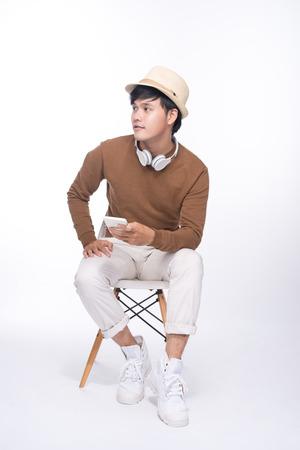 Slimme toevallige Aziatische man op stoel zittend, met smartphone in studio achtergrond