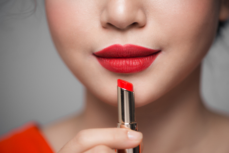 Close up portrait of attractive girl holding red lipstick over grey background Imagens