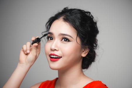 그녀의 속눈썹에 검은 마스카라를 만지고 아름다운 소녀의 근접 촬영의 초상화