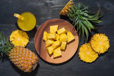 Hoogste mening van glazen ananassap en ananasfruit op een zwarte houten lijst