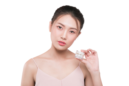 Asian young woman with perfact skin holding cosmetic product.