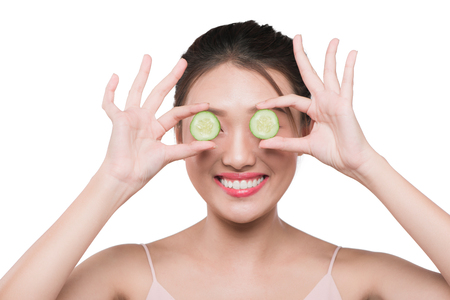 Beautiful young asian woman with cucumber slices Stockfoto