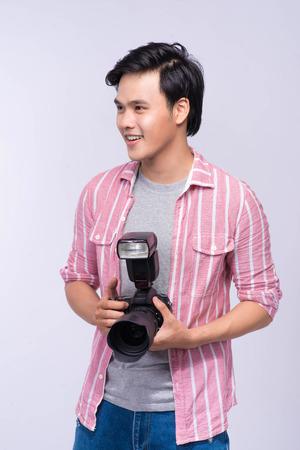 Giovane fotografo asiatico che tiene macchina fotografica digitale, mentre lavorando nello studio Archivio Fotografico - 81776813