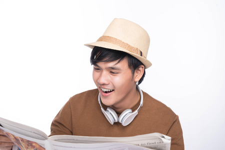 Smart casual asian man seated on chair, reading newspaper in studio background Stock Photo