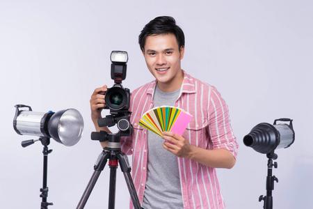 スタジオで働きながらデジタルカメラを持つアジアの若手写真家