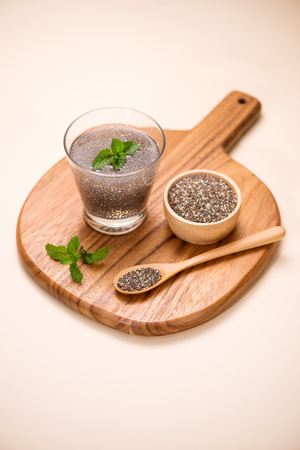 glycemic: Selective focus of chia seeds drink with water in transparent glass with lemon balm.