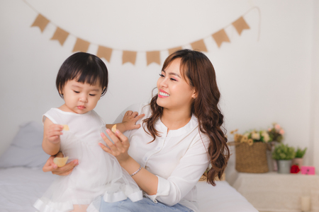 Happy loving family. Mom and child girl are having fun on the bed. Stock Photo