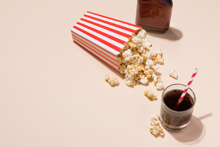 Popcorn in red and white cardboard with glass of soda Stock Photo