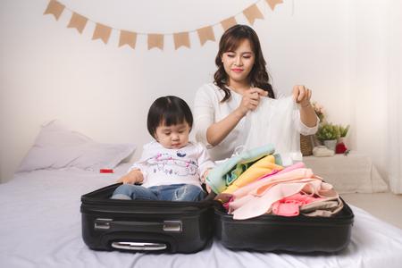 アジア ママと赤ちゃん少女スーツケース荷物と服にバカンス旅行の準備