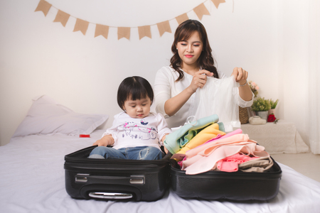 Asian mom and baby girl with suitcase baggage and clothes ready for traveling on vacation Stock fotó - 81651923