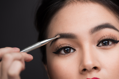 Close up of beautiful face of young asian woman getting make-up. The artist is applying eyeshadow on her eyebrow with brush Stockfoto