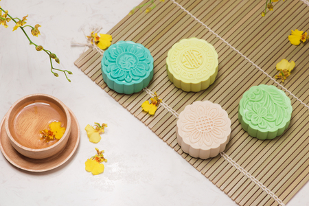 Sweet color of snow skin mooncake. Traditional mid autumn festival foods with tea on table setting. Stock fotó