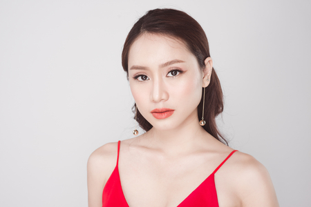 Portrait of stylish asian woman wearing red dress on grey background. Stockfoto