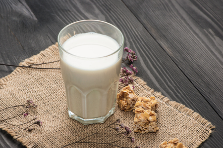 Dairy products. A glass of milk serve with almond candies on a rustic wooden table.