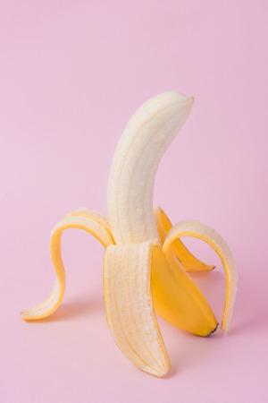 ピンクの背景に皮をむいたバナナ