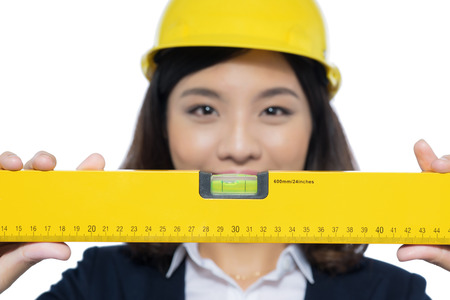 Smiling architect woman holding yellow ruler isolated on white.